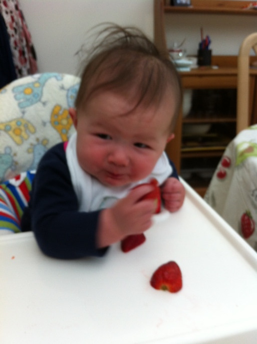 Arddun pulling a face while holding her strawberry half.
