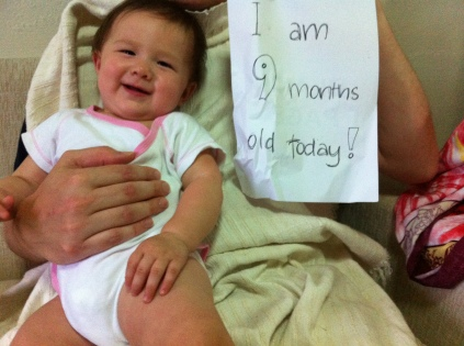 "Arddun sitting in Daddy's lap with sign ""I am 9 months old today!"""