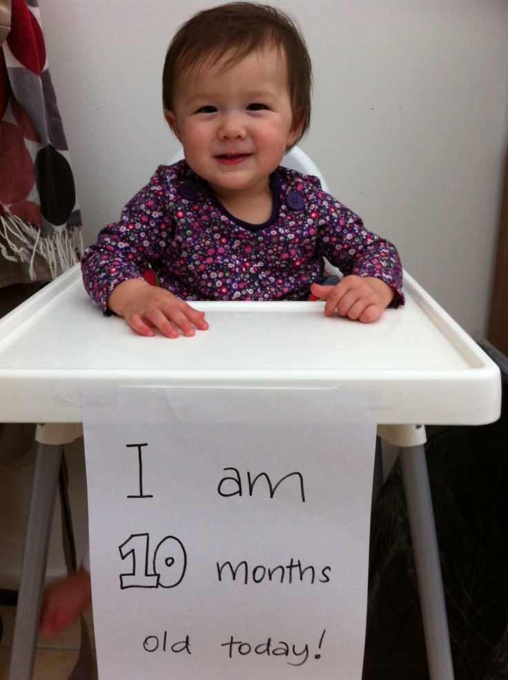 Arddun on highchair with 10 month sign