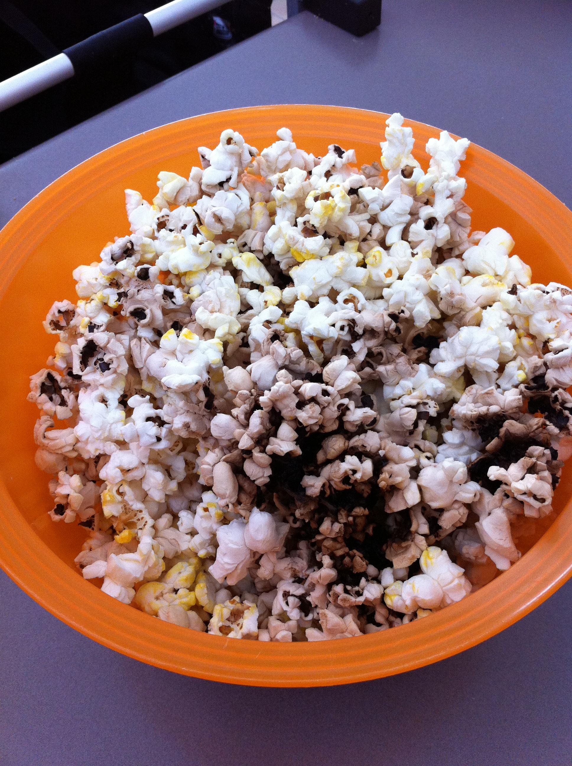 An orange bowl of burnt popcorn