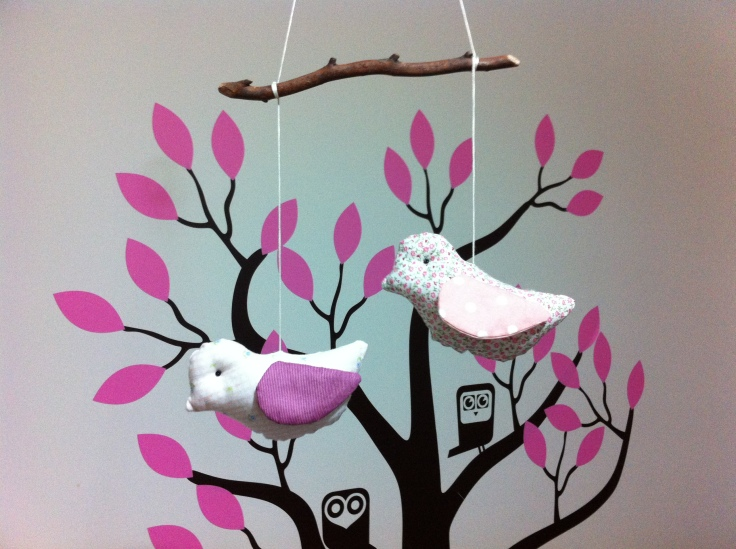 Handmade bird mobile over cot