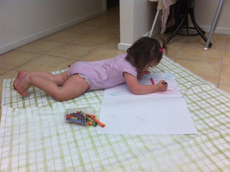 Arddun lying on floor and drawing with crayons on mat.