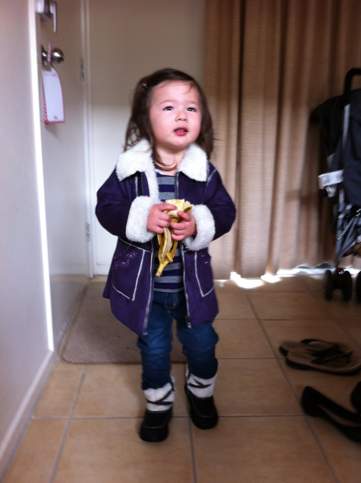 Arddun in purple coat holding banana