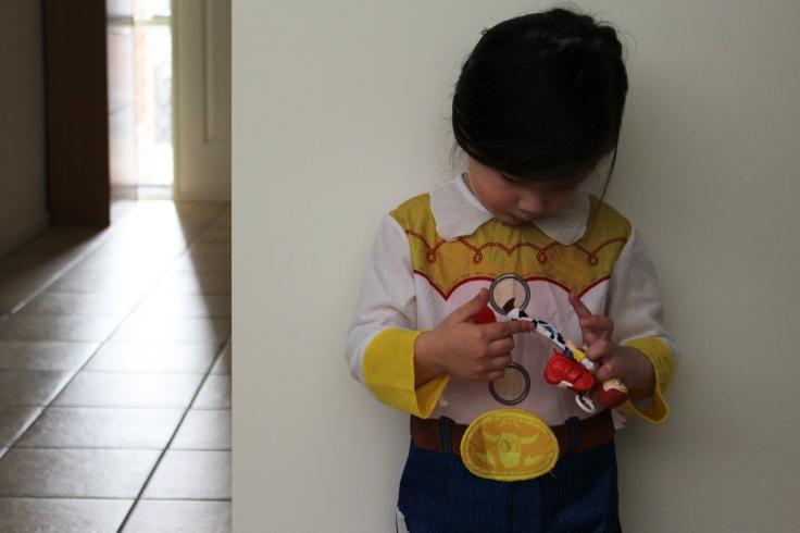 Arddun in Jessie costume looking at Jessie doll