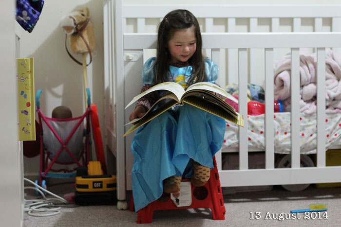 Arddun sitting on a red stool and reading in her room