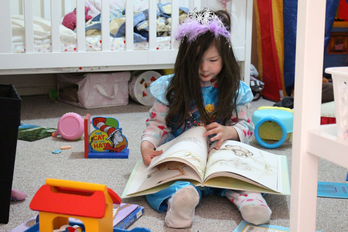 Arddun reading to herself in her bedroom while dressed as a princess