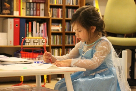 Arddun dressed as Elsa colouring at table