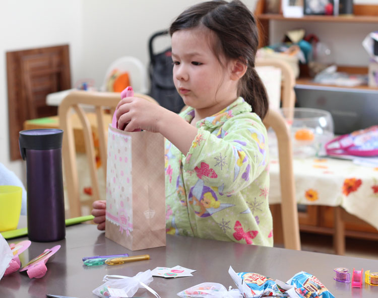 Arddun, putting together goodie bags for her friends. Loot includes chocolate chip teddy bears, colourful beads to make jewellery, temporary tattoos, and stationery.