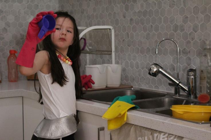 Arddun inspecting measuring cup during dishwashing