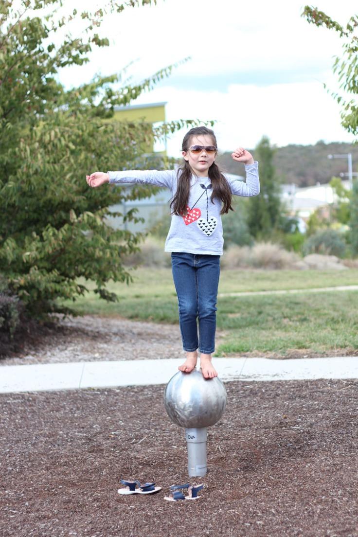 Arddun balancing on bouncing silver ball at playground